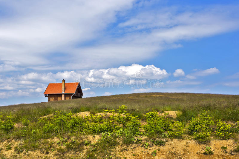 Landscape with green field house and sky. Landscape with house on green hill against cloudy summer sky royalty free stock image