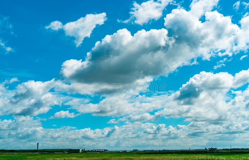 Landscape green grass field and wire fence of the airport and beautiful blue sky and white fluffy clouds. Nice weather. Nature l stock photos