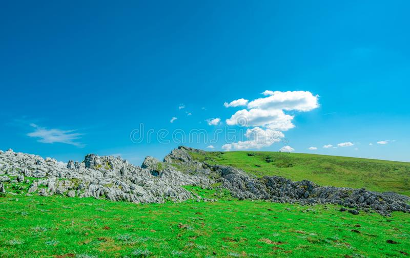 Landscape of green grass and rock mountain in spring with beautiful blue sky and white clouds. Countryside or rural view. Five people trekking on the mountain royalty free stock photos