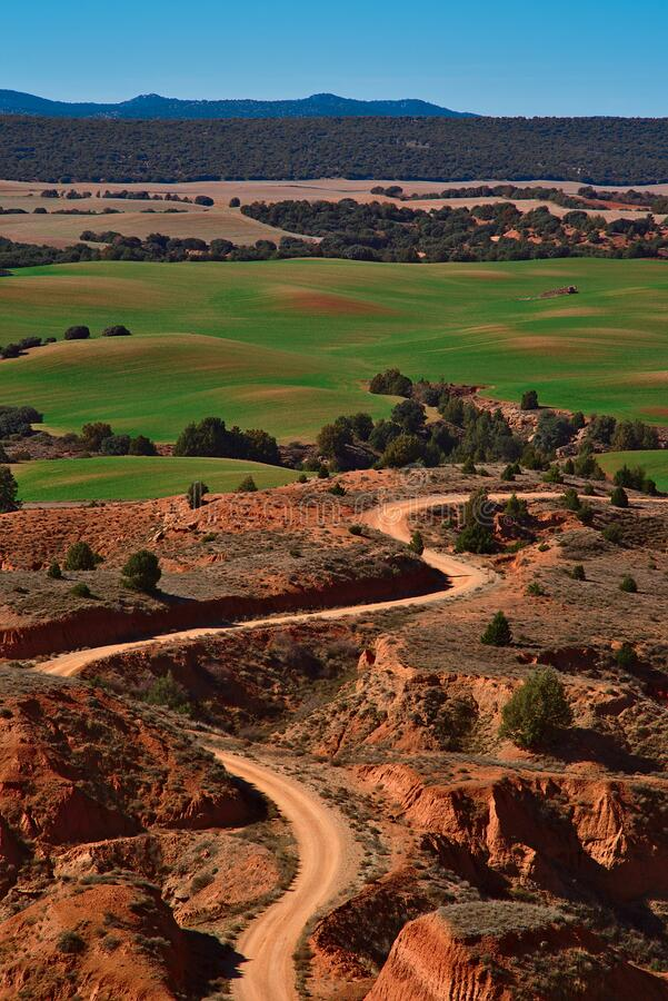 Landscape of green meadows and path through arid terrain stock images