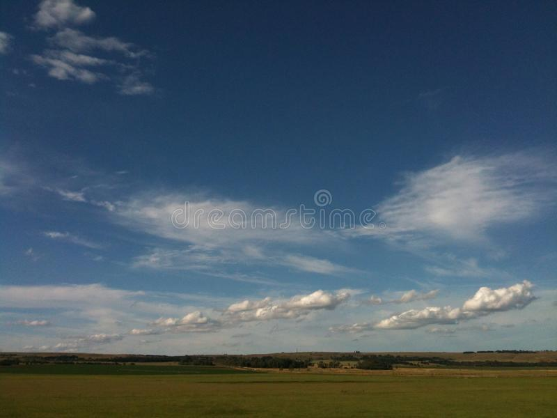 Landscape with green pastures, blue skies and scattered clouds. Agricultural landscape against a blue sky with scattered clouds royalty free stock images