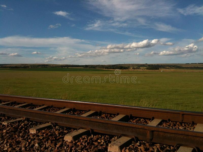 Landscape with green pastures, blue skies, scattered clouds and a railway line. Railway line in a landscape against a blue sky with scattered clouds royalty free stock image