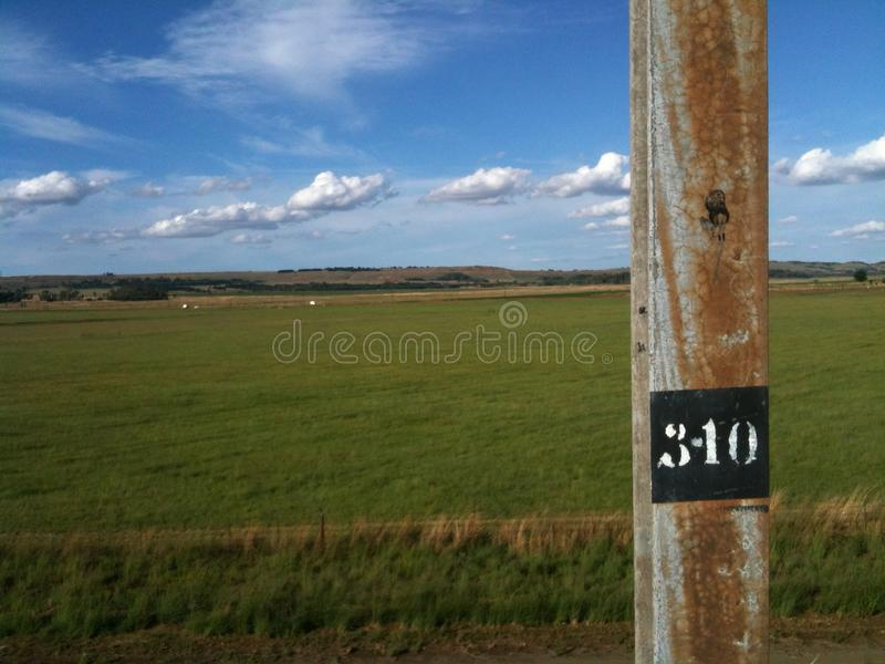 Landscape with green pastures, blue skies, scattered clouds and a railway line. Agricultural landscape against a blue sky with scattered clouds royalty free stock image