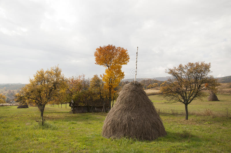 Landscape with haystack. Orchard with haystack and old shelter house in the fall season royalty free stock photos