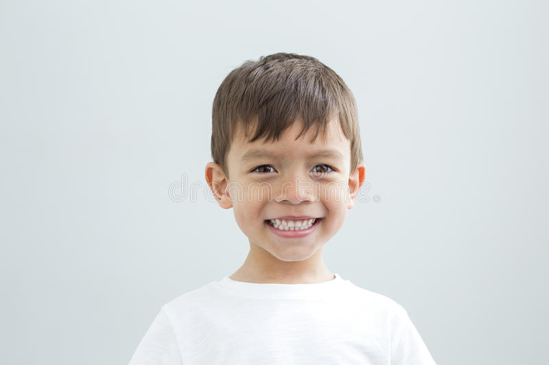 Landscape head shot of a young boy. On a plain background. He is smiling at the camera royalty free stock images