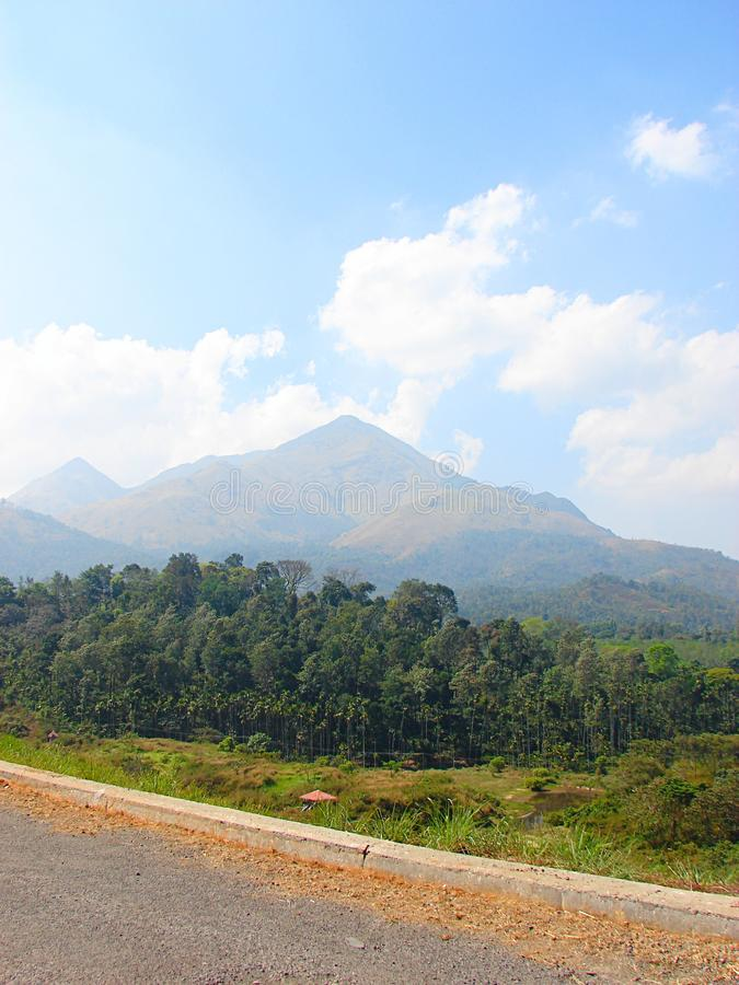 A Landscape with Hills, Trees, and a Roadside - Natural Background. This is a photograph of Banasura hills, captured along with trees and roadside, creating a royalty free stock images