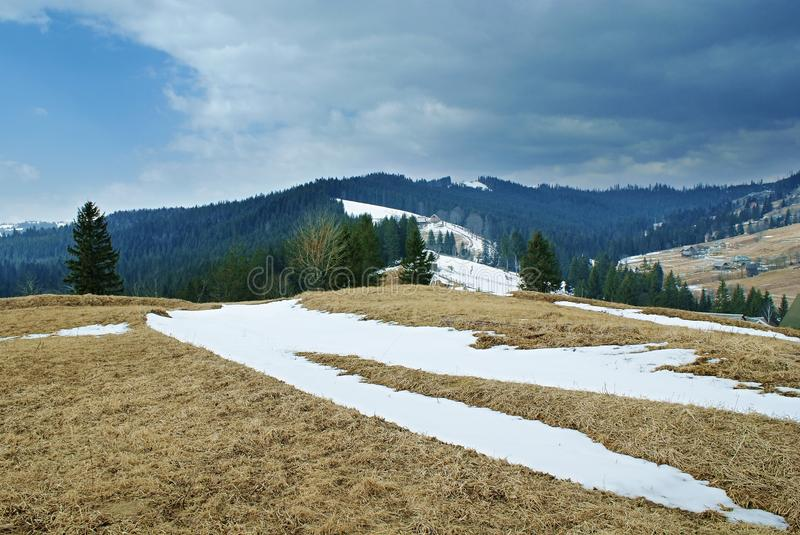 Landscape at hillside with snow and clouds in countryside. Landscape on the hillside with the last snow in the countryside in the Carpathians. Dark clouds on royalty free stock photo