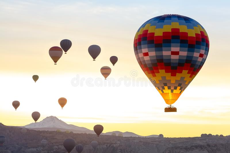 Landscape hot air aerostat in the air. Color aerostat in the foreground. Many balloons in the air against the sunrise royalty free stock image