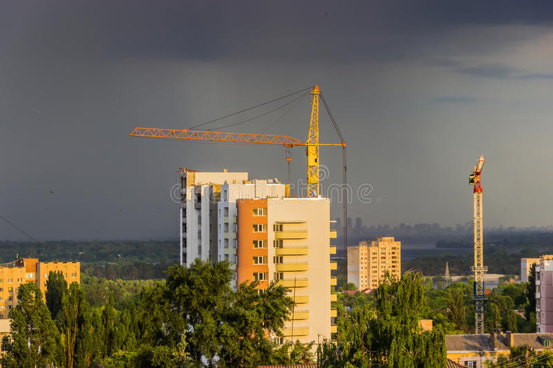 Landscape with a house under construction. Landscape with the construction of multi-storey house in a picturesque place on the background of storm clouds royalty free stock image