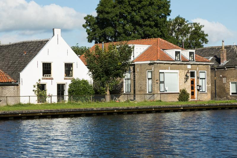 Dutch typical houses by the river bank royalty free stock photography