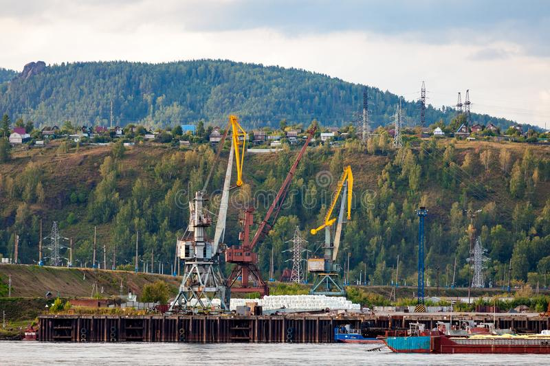 Landscape of a huge industrial construction. Several working cranes on the river, barges with cargo and on a background of a industrial city with small houses stock image