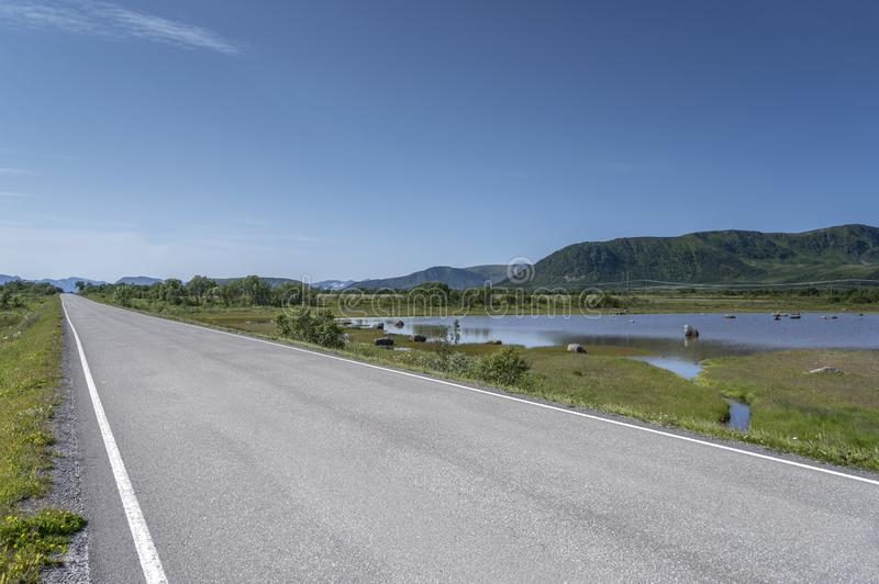Empty road by swamp on fjord shore at Sellevollvalan, Norway stock photos