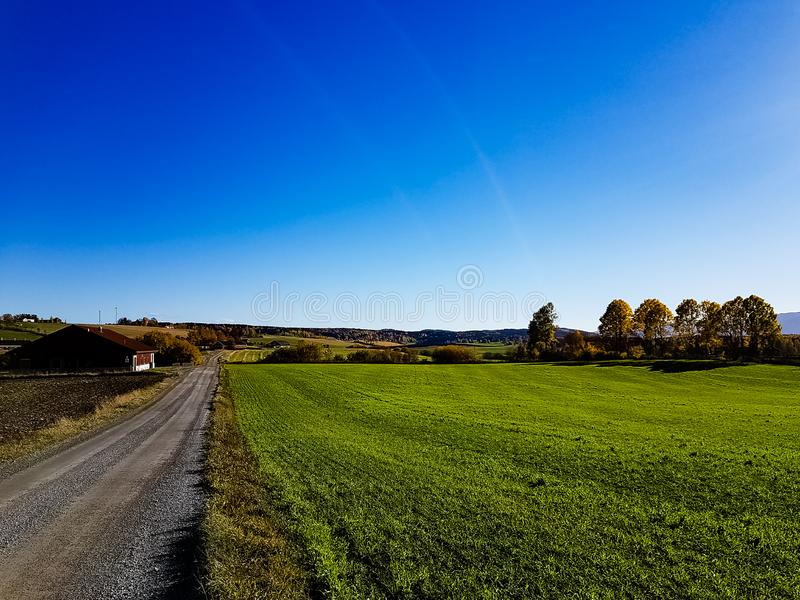 Landscape image in the Autumn. Green field alonge a dirt road in Stange Hedmark county Norway stock image