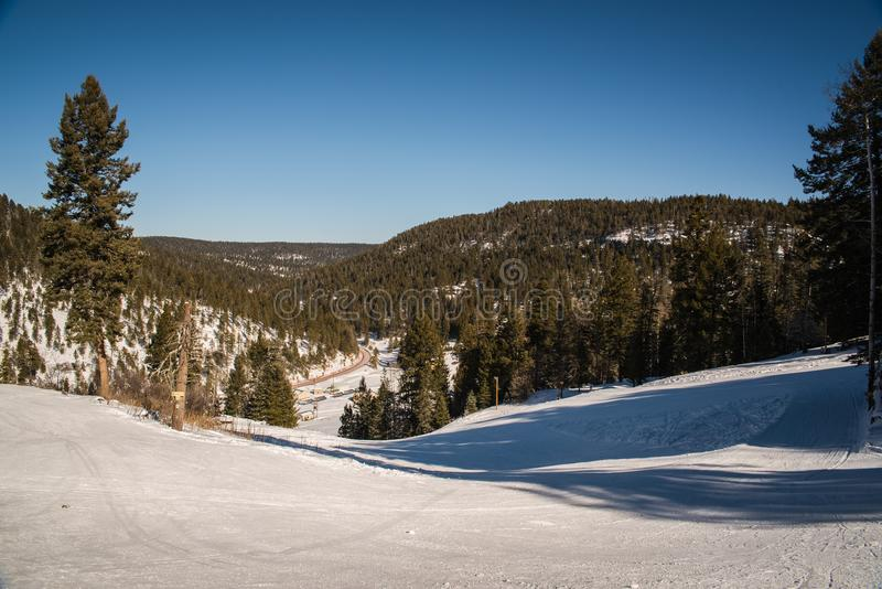 Landscape image in a snow covered forest. A snow covered ski run in Cloudcroft, New Mexico during the winter on a sunny day royalty free stock images