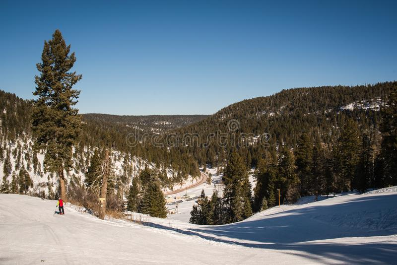 Landscape image in a snow covered forest. A snow covered ski run in Cloudcroft, New Mexico during the winter on a sunny day stock photo