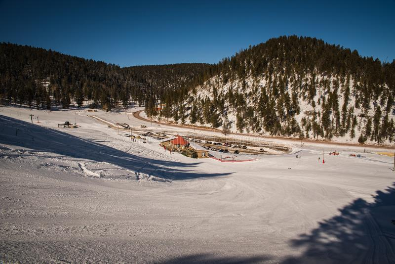 Landscape image in a snow covered forest. A snow covered ski run in Cloudcroft, New Mexico during the winter on a sunny day stock photos