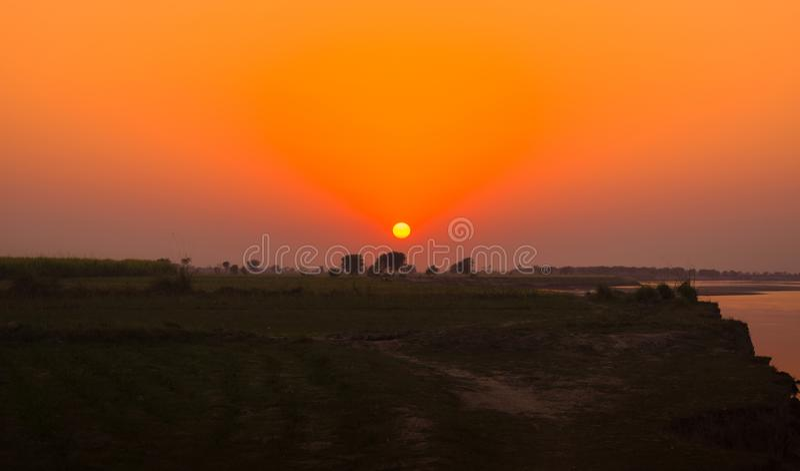 Landscape image of sun set on green fields royalty free stock image