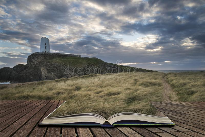 Landscape image of Twr Mawr lighthouse with windy grassy footpath in foreground at sunset concept coming out of pages in book. Landscape image of Twr Mawr royalty free stock image