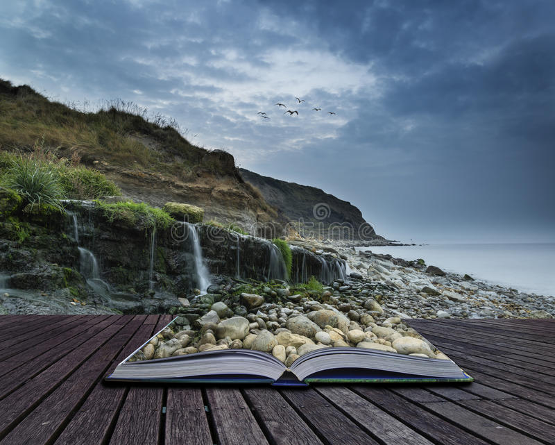Landscape image of wide waterfall flowing onto rocky beach at sunrise conceptual book image stock images