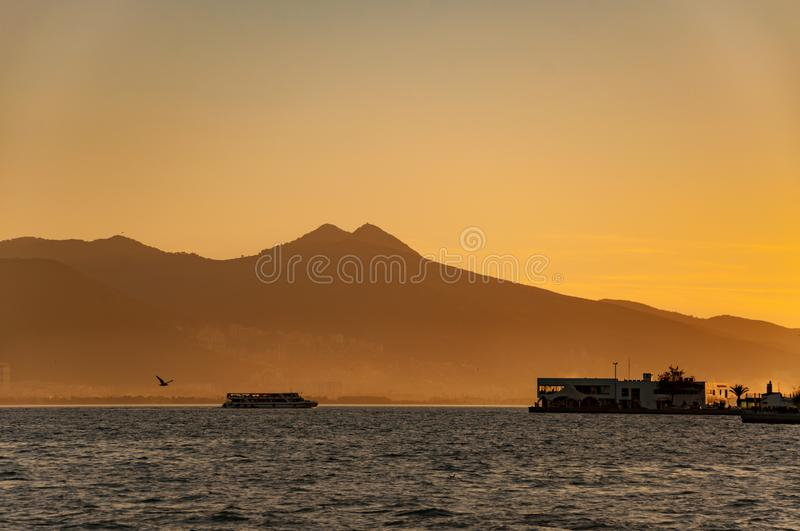 Landscape of Izmir city, foggy mountains, seagull and passenger ship at sunset royalty free stock photos