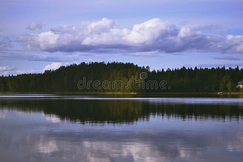 Landscape with lake, blue sky, beautiful clouds. And reflection in the water stock photography