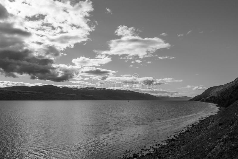 Landscape of a lake light clouds and sky. Black and white Scotland loch ness island stock photo