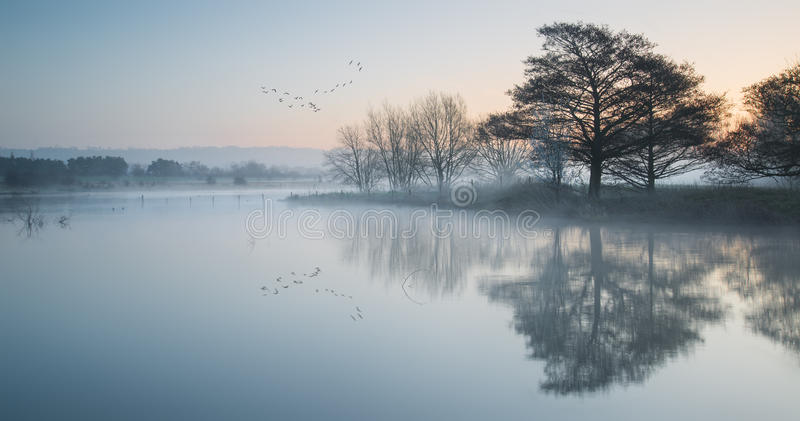 Landscape of lake in mist at sunrise royalty free stock images