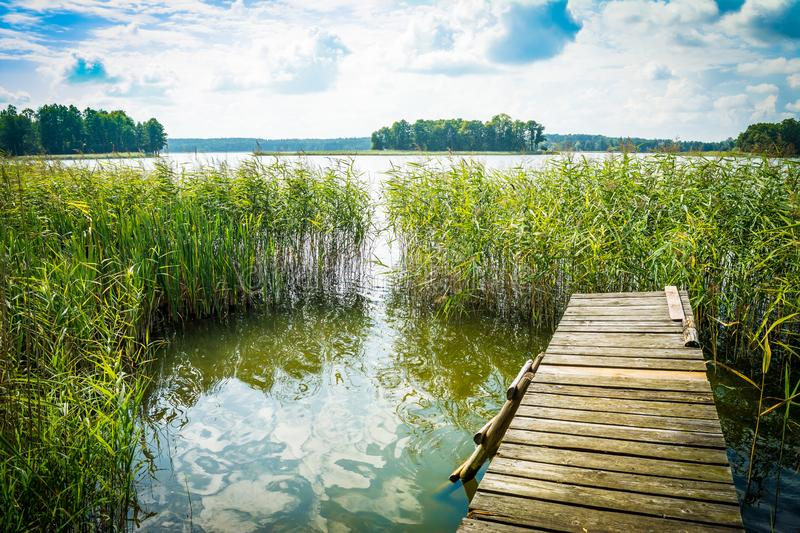 Landscape with a lake and an old bridge, a platform, a ladder into the water on a clear sunny day.  royalty free stock photos