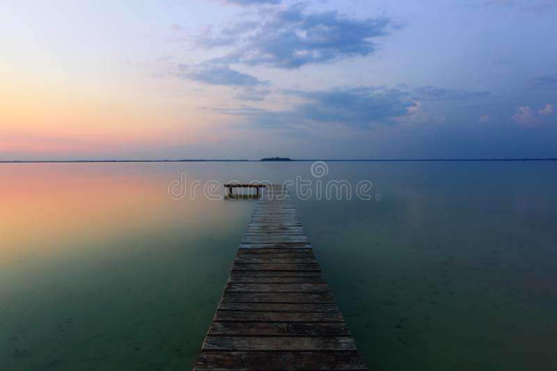 An old pier reveals views of the charmed lake, blue sky with cloud. Sunrise enlightens the horizon with orange warm colors. Landscape with a lake, old trees by stock photography