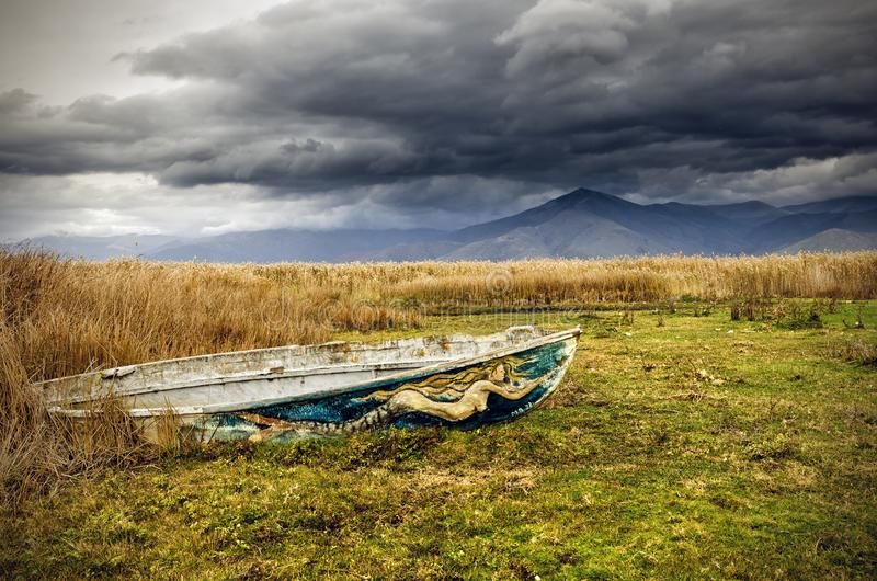 Old Boat in Prespes, Greece. Landscape in the lake of Prespes with an old boat and fields royalty free stock images