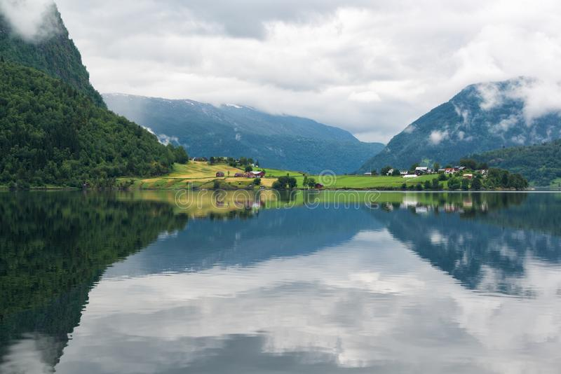 Landscape with lake and rural land with coloured houses, mirror reflection of the mountains in the water, Norway stock photo