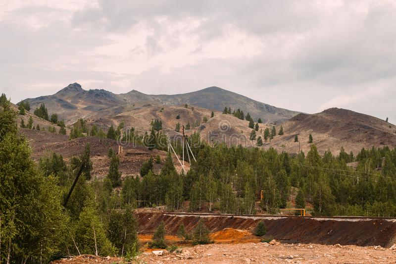 Landscape with red soil polluted copper mining factory in Karabash, Russia, Chelyabinsk region. Landscape with landscape with bald mountains polluted copper royalty free stock photography