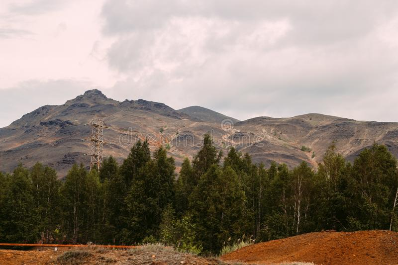 Landscape with red soil polluted copper mining factory in Karabash, Russia, Chelyabinsk region. Landscape with landscape with bald mountains polluted copper stock images