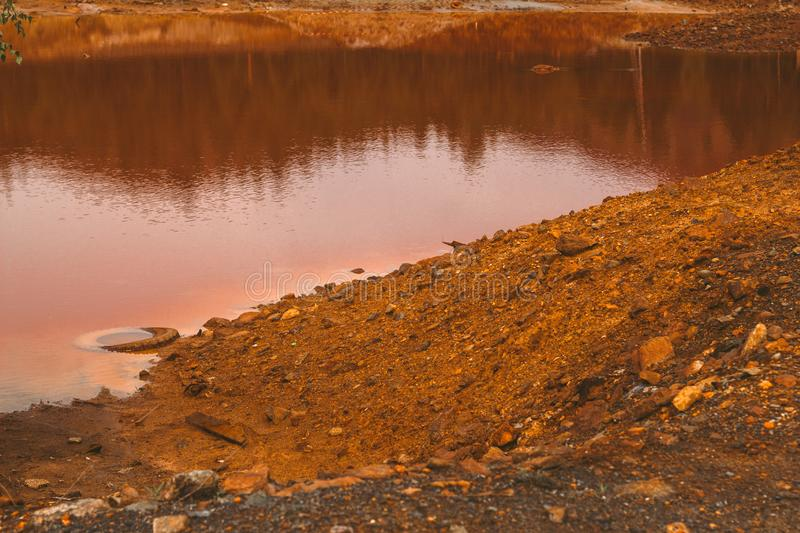 Landscape with red soil polluted copper mining factory in Karabash, Russia, Chelyabinsk region. Landscape with landscape with red water and soil  polluted by royalty free stock photography