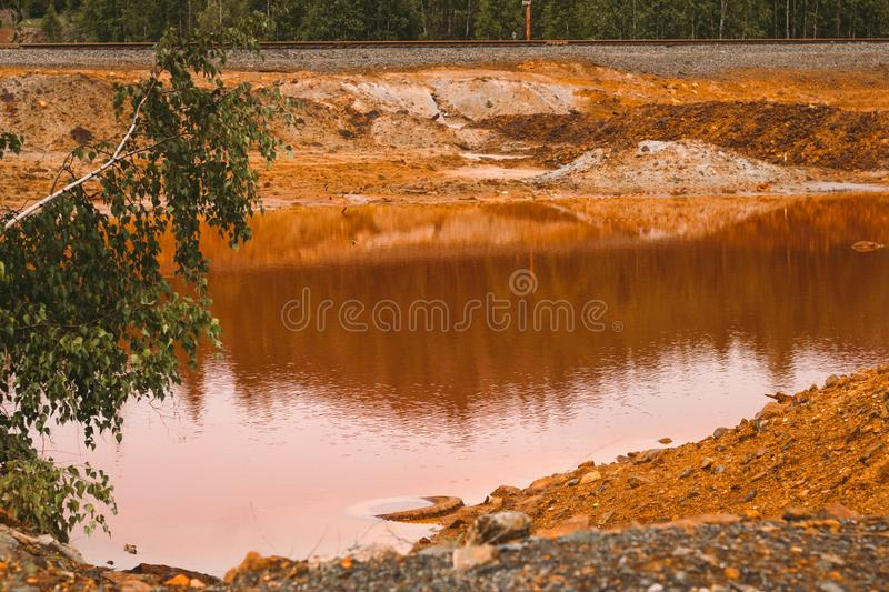 Landscape with red soil polluted copper mining factory in Karabash, Russia, Chelyabinsk region. Landscape with landscape with red water and soil  polluted by stock image