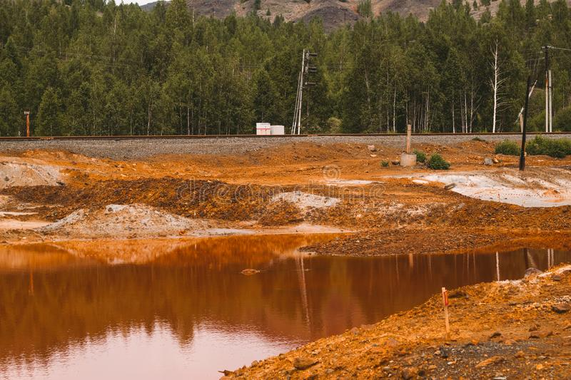Landscape with red soil polluted copper mining factory in Karabash, Russia, Chelyabinsk region. Landscape with landscape with red water and soil  polluted by royalty free stock photo