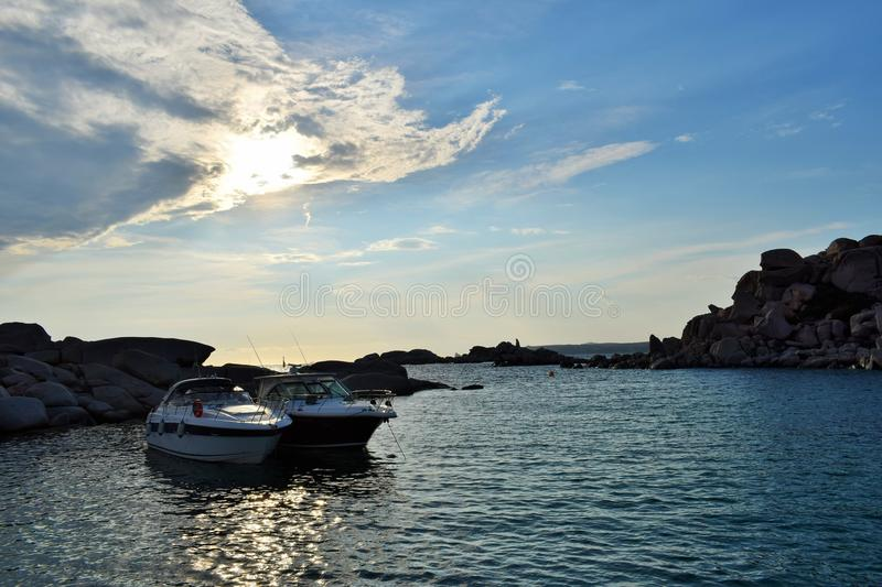 Landscape of the Lavezzi islands in Corsica France. Beautiful landscape of the sea with boats and the sun hidden by clouds in the Lavezzi islands in Corsica stock image