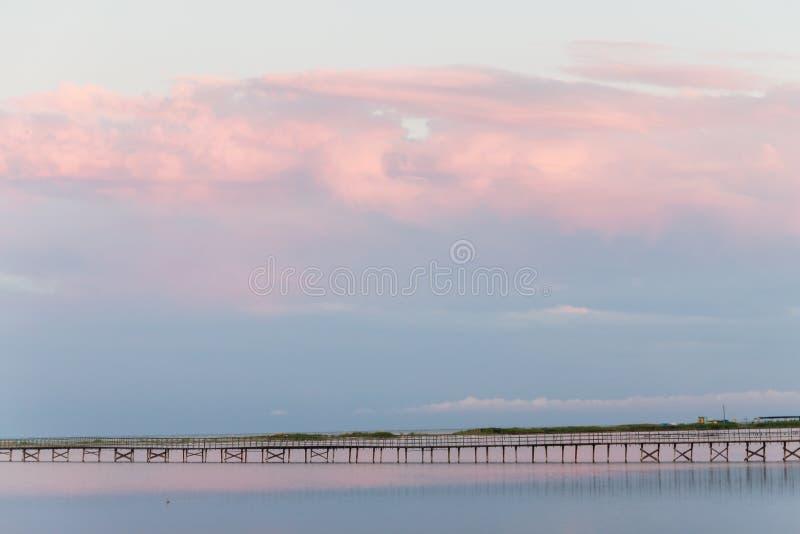 Landscape long bridge over a sea plait on a beautiful pink sunset stock photo