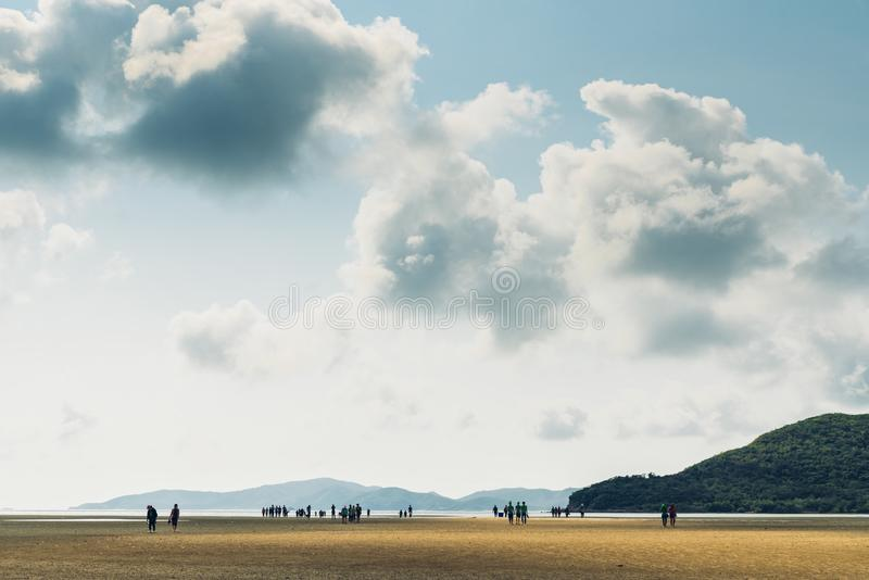 Landscape of low tide with green mountain, cloud sky with people in background at Toong Pronge Bay in Chon Buri. royalty free stock images
