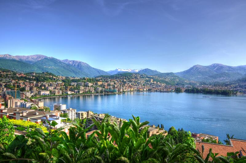 Landscape of Lugano surrounded by an Alpine Lake under the sunlight in Ticino in Switzerland. A landscape of Lugano surrounded by an Alpine Lake under the royalty free stock photo