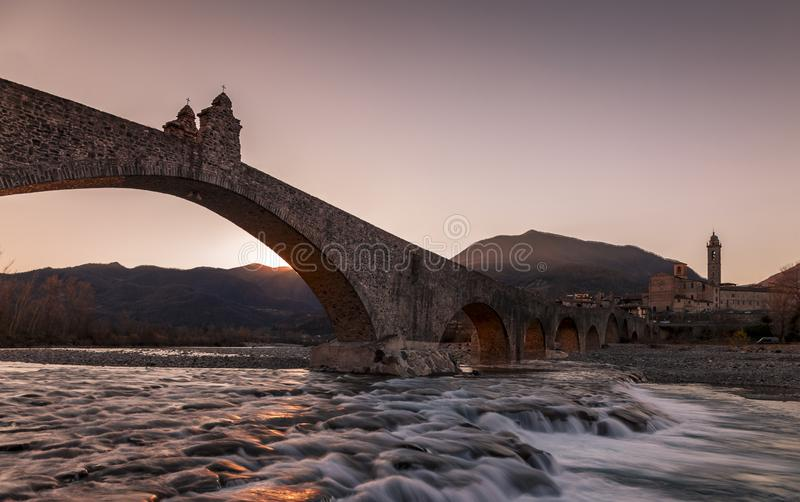 Landscape of a medieval bridge over a turbulent river at sunset royalty free stock image