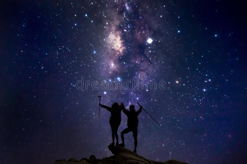 Landscape with Milky Way. Night sky with stars and silhouette of a couples. Happy hikers climbing up mountain cliff on the mountain stock photography