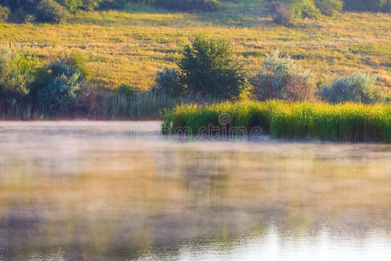 Landscape with misty morning on lake or pond. Nature, park, environment, fog, haze, smoke, outdoor, river, spring, sunlight, sunrise, tranquil, sky, water royalty free stock photo