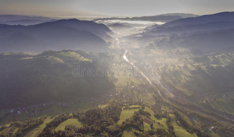 Landscape misty panorama. Fantastic dreamy sunrise on rocky mountains with view into misty valley below. Foggy forest hills. View royalty free stock images