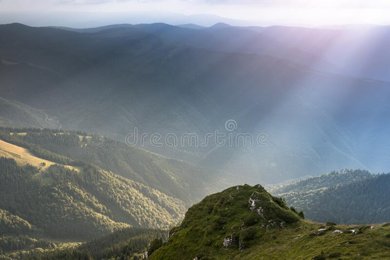 Landscape of mountain range with visible silhouettes through the morning colorful fog in the rays of the sun. Sunrise in the mount. Landscape of mountain range stock image