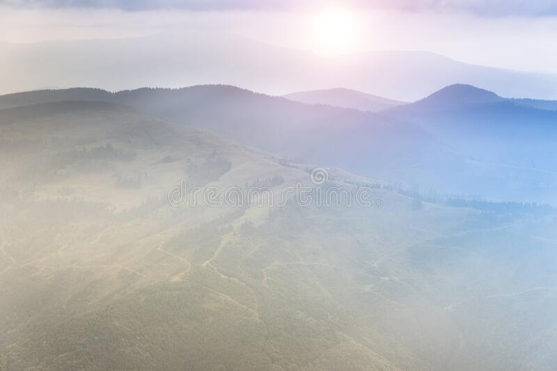 Landscape of mountain range with visible silhouettes through the morning colorful fog. Sunrise in the mountains. Filtered image:cross processed retro effect royalty free stock images