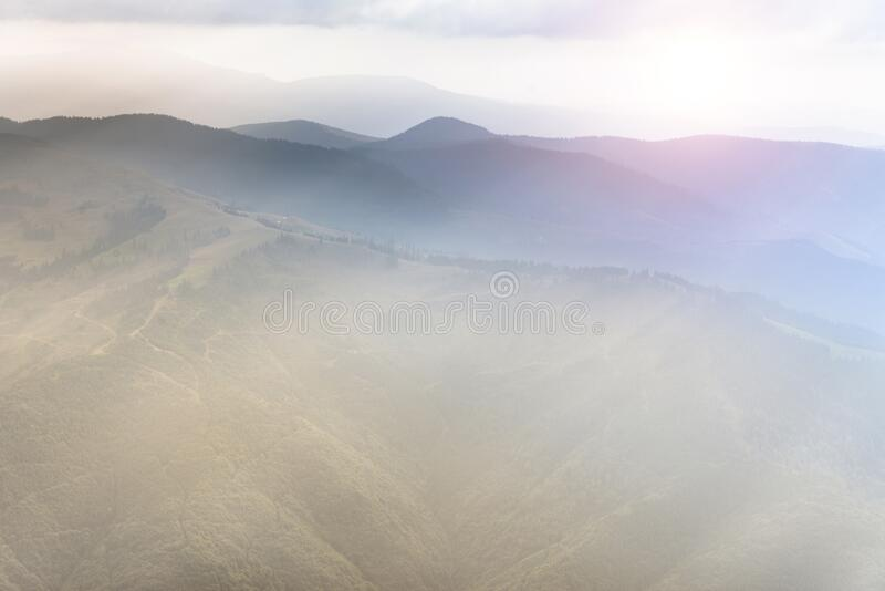 Landscape of mountain range with visible silhouettes through the morning colorful fog. Sunrise in the mountains. Filtered image:cr. Oss processed retro effect stock photo