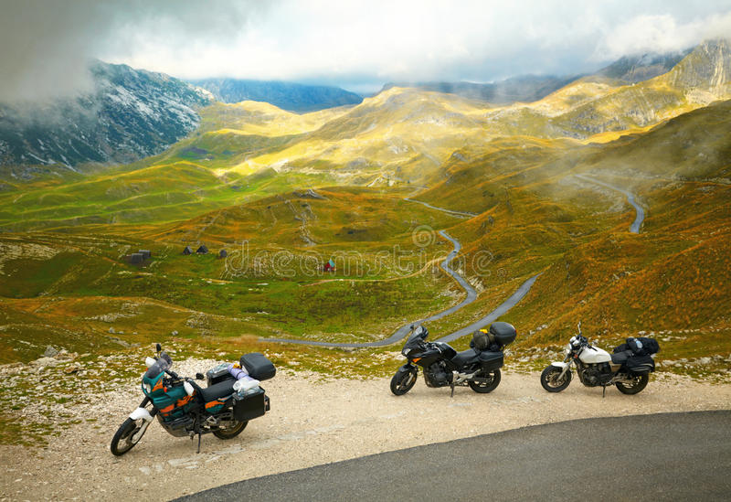 Landscape with mountain road and three motorbikes. Sunset clouds royalty free stock images