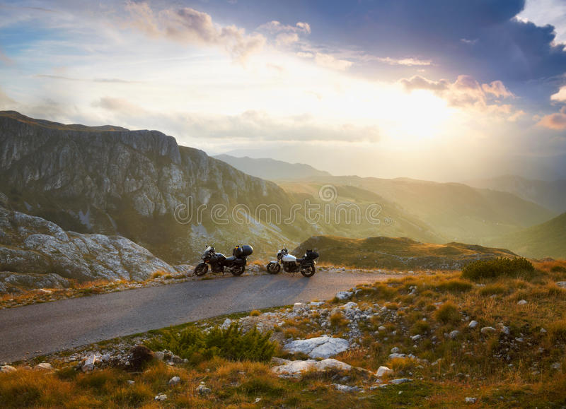 Landscape with mountain road and two motorbikes. Sunset clouds royalty free stock photography
