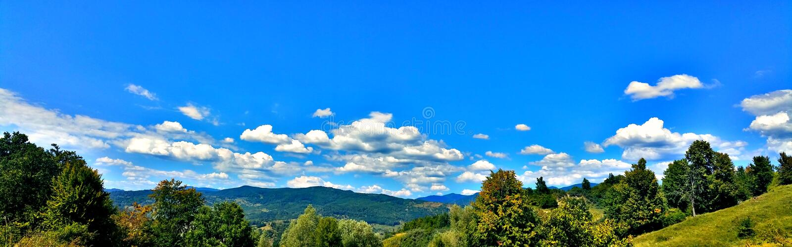 Landscape, mountain, trees, sky and clouds stock image